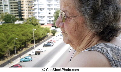 Old retired woman watching traffic through window -...