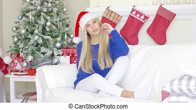 Adorable blond girl sitting on sofa in Santa Claus hat at...