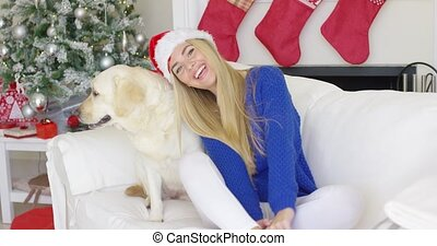 Christmas girl with her dog friend at the couch waiting for...
