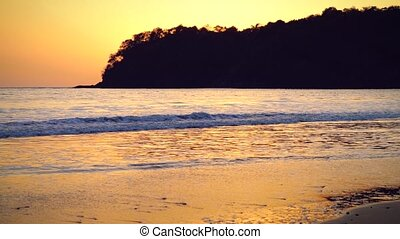 Dreamscene. Golden ocean waves at the sunset in tropics.