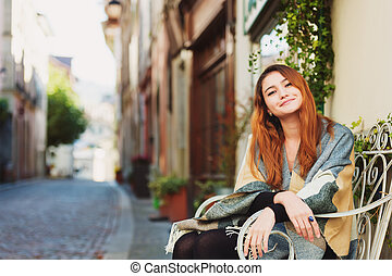 Young fashion 20 year old girl sitting on the bench, wearing...
