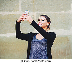 Young 20 year old girl taking selfie with her phone