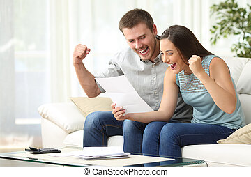 Excited couple reading a letter at home - Excited couple...