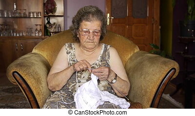 Old retired woman knitting in home - Retirement Home -...