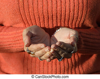 Woman in Orange Sweater with Cupped Hands - Photo of a woman...