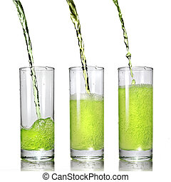 green juice pouring into glass isolated on white