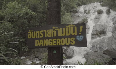 Video of Dangerous sign over waterfall background - video in...