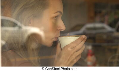 Girl drinking coffee in cafe - Blond girl drinking coffee in...