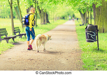 Woman runner walking with dog in summer park