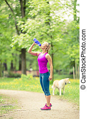 Woman running and jogging with dog in green summer park and woods