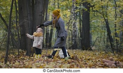 Happy family concept - little daughter with her mother plays with yellow leaves in autumn forest - shakes the tree, piled leaves