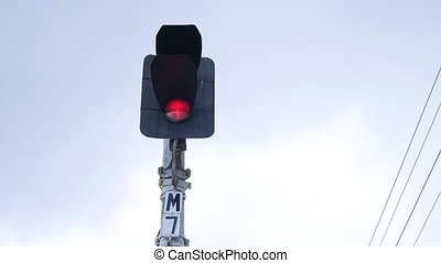 Traffic light shows red signal on railway on a gray...