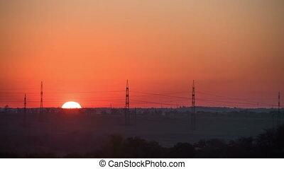 Sun Rises over the Horizon. Time Lapse. Big red sun rises...