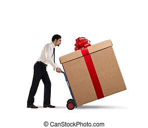Delivery xmas gifts - Businessman pushes heavy great gift...