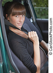fasten seat belt in car - young woman holding fasten seat...