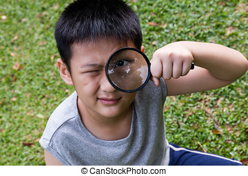 Happy Asian Chinese little boy looking through magnifying glass