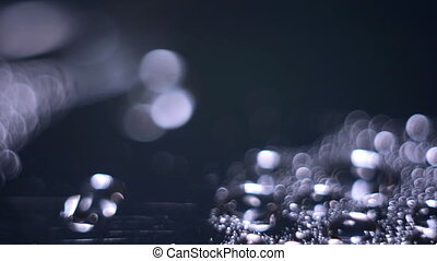 Water moves on the shiny surface. Abstract background bokeh