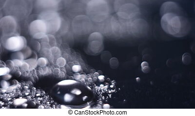 Drops of water shaking in the wind on a shiny surface....