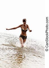 happy girl run in the water