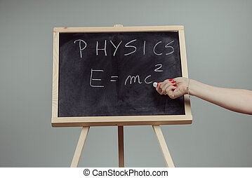 Physics word and formula E=mc2 on chalkboard - Handwritten...
