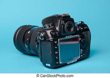 Professional modern DSLR camera against blue background