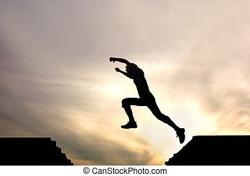 silhouette of jumping boy against sky