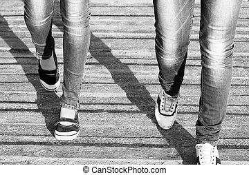 The legs of two girls in jeans and comfortable shoes while...
