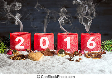 Four blown out advent candles with 2016 in snow - Four red...