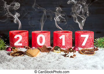 Four blown out advent candles with 2017 in snow - Four red...