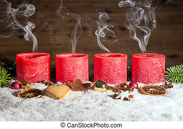 Four blown out advent candles in snow - Four red blown out...