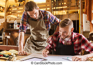 workmen with tablet pc and blueprint at workshop -...