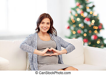happy pregnant woman making heart gesture at home -...