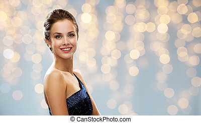 smiling woman in evening dress over lights - people,...