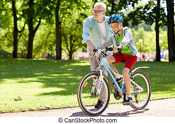 grandfather and boy with bicycle at summer park - family,...