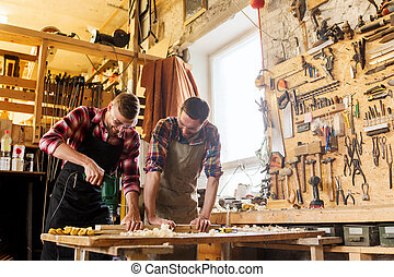 carpenters with drill drilling plank at workshop -...