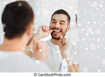 man with dental floss cleaning teeth at bathroom - health...