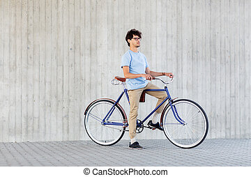 young hipster man riding fixed gear bike - people, style,...