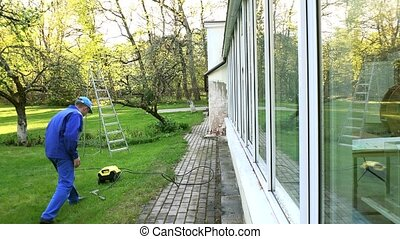 Man washing conservatory window with water jet reflecting on...