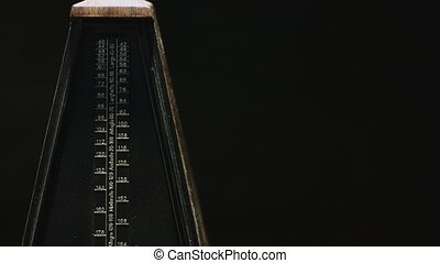 Vintage metronome beats the rhythm - Close-up shot of...