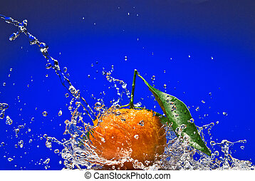 Tangerine with green leaves and water splash on blue...