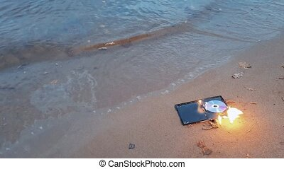 data cd disc in fire on the sand at coast 4k