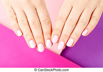 Female hand with manicure on a colorful background