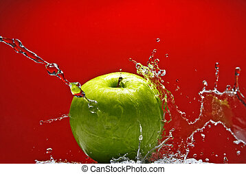Green apple with water splash on red background