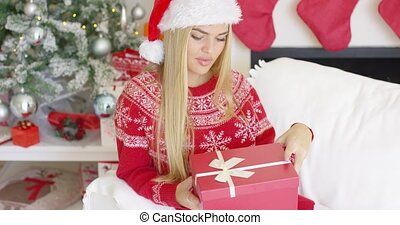 Pretty smiling blondie looking at her boxed christmas gift...