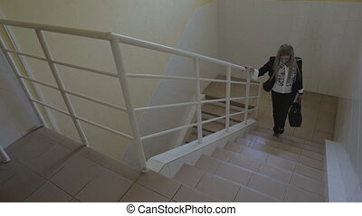 Beautiful young business woman climbs the stairs to office stock footage video