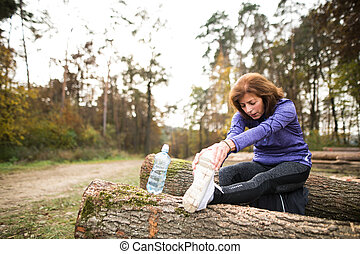 Senior runner sitting on wooden logs, stretching, drinking...