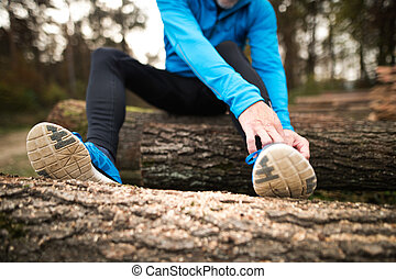 Unrecognizable runner sitting on wooden logs, man resting,...