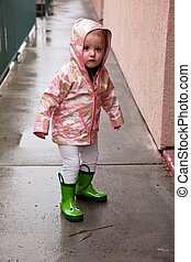 Rain gear - Cute caucasian baby girl wearing pink raincoat...