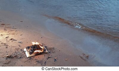 Burning book on the sand at coast 4k