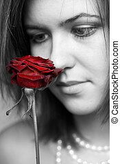 black and white portrait of woman looking at red rose